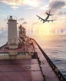 Het algemene vrachtschip argosy kruisen op oceaan met vliegtuig aan stedelijk Stock Foto's
