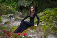 Het alleen mooie meisje zit op groen mos in een feebos royalty-vrije stock afbeelding