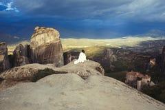 Het alleen wijfje in de witte plaid op de rand van de rots kijkt op de kloosters van Meteora Wijfje op de rots en de kloosters va Stock Foto's