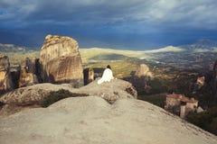 Het alleen wijfje in de witte plaid op de rand van de rots kijkt op de kloosters van Meteora Wijfje op de rots en de kloosters va Stock Foto