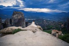 Het alleen wijfje in de witte plaid op de rand van de rots kijkt op de kloosters van Meteora Wijfje op de rots en de kloosters va Stock Afbeeldingen