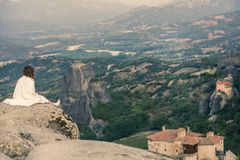 Het alleen wijfje in de witte plaid op de rand van de rots kijkt op de kloosters van Meteora Wijfje op de rots en de kloosters va Royalty-vrije Stock Afbeeldingen