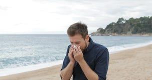 Het allergische mens niezen die op het strand lopen stock videobeelden