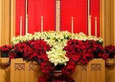 Het altaar van de kerk met poinsettia stock afbeeldingen