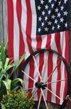 Het Amerikaanse Vlag en Wagenwiel in tuin het plaatsen stock afbeelding