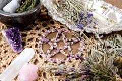 Het amethist Pentagram met droge kruidbundels, mortier en stamper op crotchet de doek van het jutealtaar - met seleniet en nam kw stock afbeelding