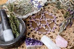 Het amethist Pentagram met droge kruidbundels, mortier en stamper op crotchet de doek van het jutealtaar - met seleniet en nam kw stock afbeeldingen