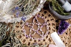 Het amethist Pentagram met droge kruidbundels, mortier en stamper op crotchet de doek van het jutealtaar - met seleniet en nam kw royalty-vrije stock afbeeldingen
