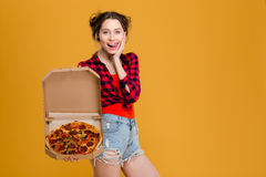 Het amuseren van aantrekkelijke jonge vrouw die tong tonen en het houden van pizza Royalty-vrije Stock Afbeeldingen