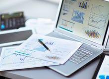 Het analyseren van investeringsgrafieken met laptop Stock Afbeelding