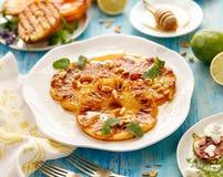 Het ananasdessert, Geroosterde plakken van ananas met de toevoeging van honing, roosterde pijnboomnoten, verse citroenbalsem en stock foto