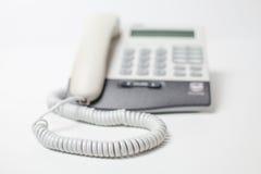 Het apparaat van de bureautelefoon met telefoonkoord wachten van vraag Kleine diepte van nadruk Stock Foto