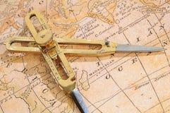 Het apparaat van de navigatie op een achtergrond een oude kaart stock foto's