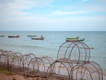 Het Apparaat van de vissenval op het overzeese strand met groeps kleine vissersboot royalty-vrije stock afbeelding