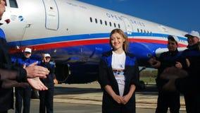 Het applaus dansende vrouw van vliegveldarbeiders tegen vliegtuig stock footage