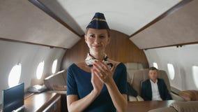 Het applaus van de vliegtuigstewardess aan camera binnen van particuliere sectorstraal stock video