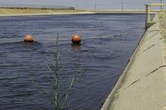 Het Aquaduct van Californië: het blauwe water stroomt voorbij een lijn van rode ballen stock foto's