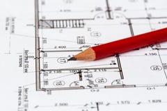 Het architecturale plan van het huis is gedrukt op een wit blad van document Een rood potlood op het stock fotografie