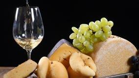 Het art. van de restaurantkaas De verscheidenheid van harde kaas bracht prachtig een samenstelling aan De wijn giet in flass in l stock videobeelden