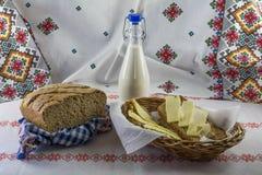 Het artisanale brood, de melkfles en de plakken paneren boter op het tafelkleed in etnische stijl Royalty-vrije Stock Foto