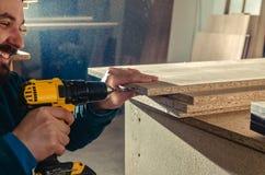 Het assembleren van meubilair van spaanplaat, die een draadloze schroevedraaier gebruiken, sluit omhoog royalty-vrije stock afbeelding
