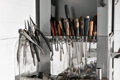 Het assortiment van doet het zelf werkende hulpmiddelen die in een kast tegen een muur hangen vuile motorolie Stock Foto's