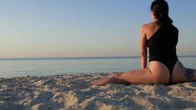Het atletische brunette in een zwart lichaam met een tatoegering op haar dij zit op de spleten en de rek door het overzees Fitnes stock video