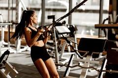 Het atletische donker-haired meisje gekleed in zwarte sportenbovenkant en borrels werkt op de geschiktheid-post in de gymnastiek  royalty-vrije stock afbeeldingen