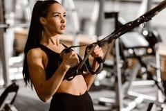 Het atletische donker-haired meisje gekleed in zwarte sportenbovenkant en borrels werkt op de geschiktheid-post in de gymnastiek  stock afbeeldingen