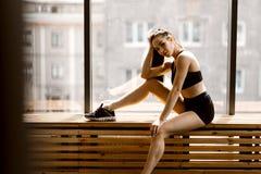 Het atletische donker-haired meisje gekleed in zwarte sportenbovenkant en borrels zit op een houten venstervensterbank in de gymn stock afbeelding