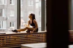 Het atletische donker-haired meisje gekleed in zwarte sportenbovenkant en borrels zit op een houten venstervensterbank in de gymn stock fotografie