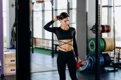 Het atletische donker-haired meisje kleedde zich in zwarte sportkledingstribunes met water in haar hand dichtbij het sportmateria royalty-vrije stock fotografie