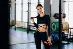 Het atletische donker-haired meisje kleedde zich in zwarte sportkledingstribunes met water in haar hand dichtbij het sportmateria stock foto's