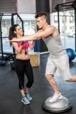 Het atletische man uitwerken bevorderd door trainervrouw Stock Afbeeldingen