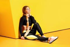 Het atletische meisje met lang blond haar gekleed in een modieuze sportkleding zit op de gele vloer naast het geel royalty-vrije stock fotografie