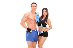 Het atletische paar stellen met waterfles Stock Foto's