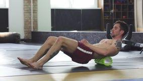 Het atletische spiermens ontspannen na opleiding, gebruikend schuimrol stock videobeelden