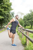 Het atletische sterke mens doen rekt zich alvorens openlucht uit te oefenen uit, stock foto