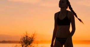 Het atletische volleyball van het meisjes speelstrand springt in de lucht en slaat de bal over het net op een mooie de zomeravond stock video