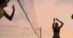Het atletische volleyball van het meisjes speelstrand springt in de lucht en slaat de bal over het net op een mooie de zomeravond stock footage
