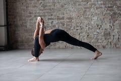 Het atletische wijfje die yoga hoge draai doen valt uit royalty-vrije stock fotografie