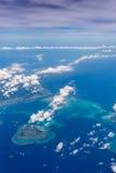 Het atoleiland in blauwe oceaan door wolken en donkerblauwe hemel Royalty-vrije Stock Foto's