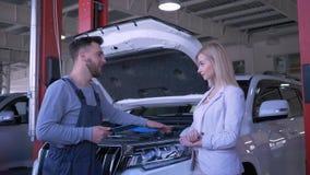 Het auto de dienstcentrum, professionele hersteller raadpleegt cliëntvrouw over gebroken auto open kap en de schok dient in stock footage