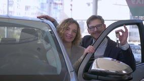 Het auto kopen, gelukkig paar in de eigenaars van het liefdevoertuig verrukt aankoop en toont sleutels in het centrum van de auto stock footage