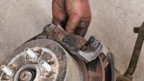 Het auto mechanische werken aan remmen in autoreparatiewerkplaats stock footage