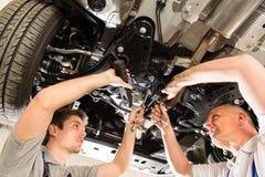 Het auto mechanische werken onder auto Stock Afbeeldingen