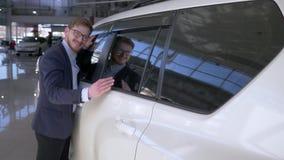 Het autohandel drijven, zalige kopersmens in glazen met plezier dat nieuw voertuig strijkt dat zacht op Autoverkoopcentrum glimla stock footage