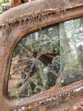 Het autokerkhof verliet roestige oude auto met gebroken venster Stock Afbeelding