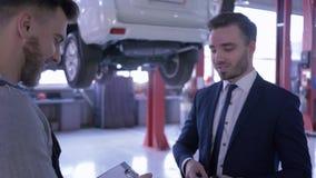 Het autoonderhoud, eigenaarvoertuig geeft de sleutels en schudt handen aan mannelijke werktuigkundige dichtbij auto op mechanisch stock footage