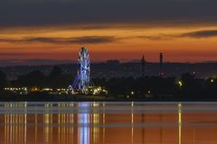 Het avondlandschap van de stad met veel lichten en ferris rijdt stock foto